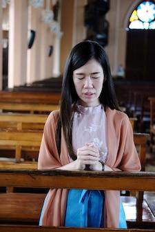 Mulher asiática sentada em uma cadeira de madeira orando em uma igreja cristã
