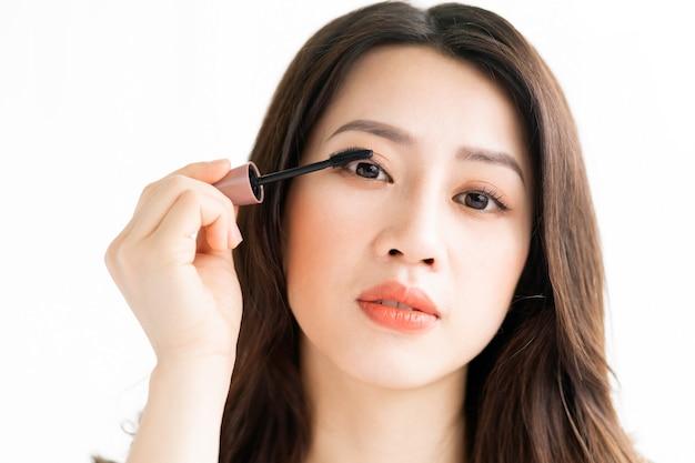Mulher asiática sentada maquiada em frente ao espelho
