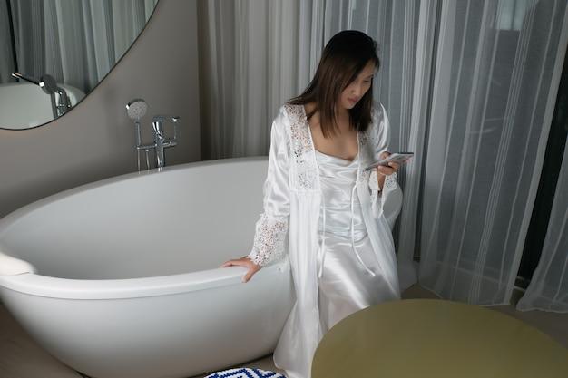Mulher asiática sentada na banheira à noite em uma camisola branca e um robe de seda com um telefone celular na acomodação. dependência de smartphone. sem dormir