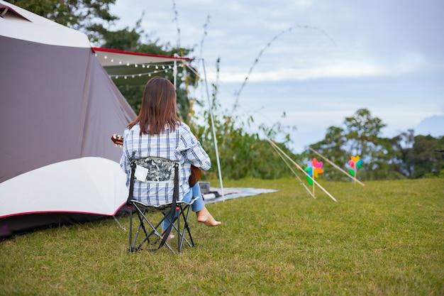 Mulher asiática sentada na cadeira de piquenique e tocando violão enquanto acampava com a família no local de acampamento na bela natureza.