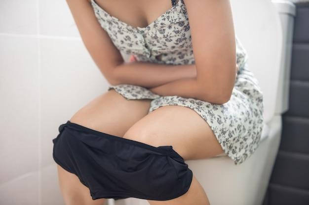 Mulher asiática sentada na sanita no banheiro e segurando seu estômago doloroso de estoma ruim