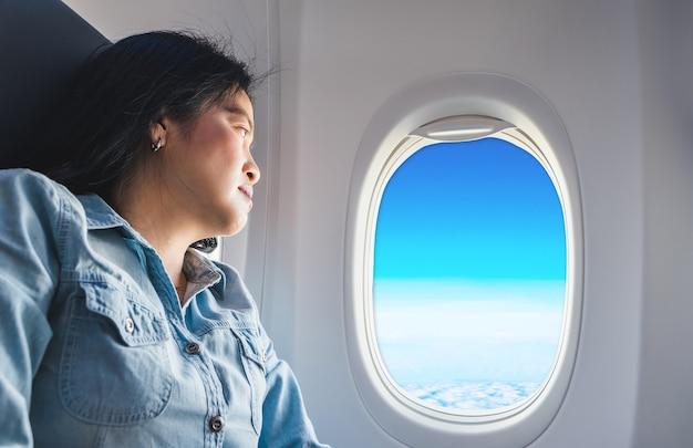 Mulher asiática sentada no assento da janela no avião e olhe para fora da janela veja o céu azul