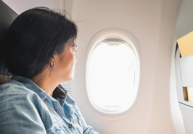 Mulher asiática sentada no assento da janela no avião e vista fora da janela