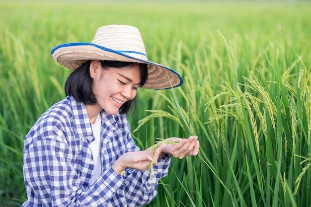 Mulher asiática sentada no campo segurando arrozais verdes com uma cara sorridente.