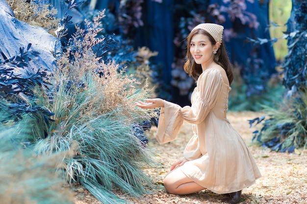 Mulher asiática sentada no chão e admirando com uma flor no jardim azul e a floresta como pano de fundo