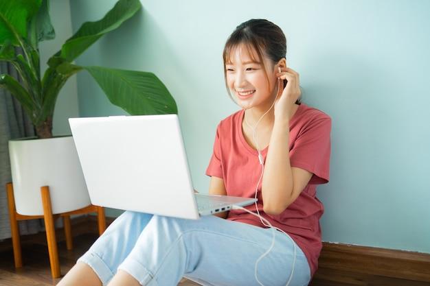 Mulher asiática sentada no chão enquanto trabalha em casa