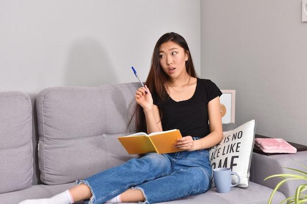Mulher asiática sentada no sofá e um caderno laranja