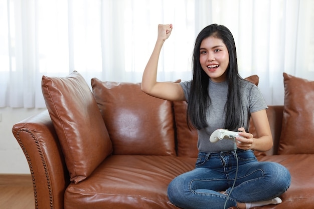 Mulher asiática sentada no sofá, segurando o joystick e jogando o jogo.
