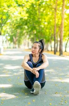 Mulher asiática sentada relaxando em roupas esportivas após o exercício no parque