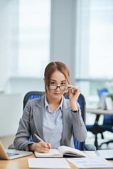 Mulher asiática, sentado à mesa no escritório, escrevendo na agenda e olhando para cima acima de óculos