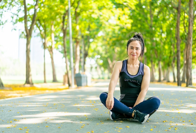 Mulher asiática, sentado e relaxe em sportwear após o exercício no parque