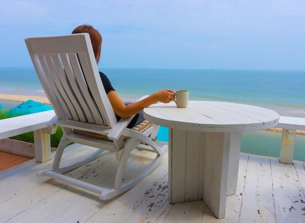 Mulher asiática, sentado na cadeira de praia de madeira branca