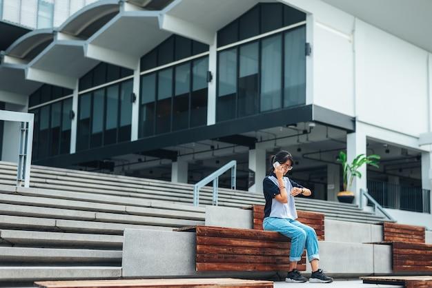 Mulher asiática, sentando, ligado, a, escadaria, usado, telefone esperto, lê