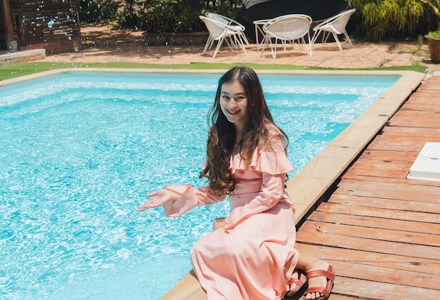 Mulher asiática sentar ao lado da piscina azul desfrutar de jogar respingos de água em dia ensolarado. relaxe no verão.