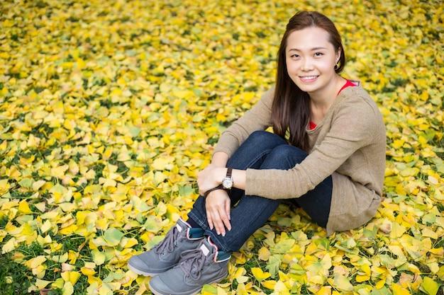 Mulher asiática sentar no fundo de folhas de ginkgo no jardim.