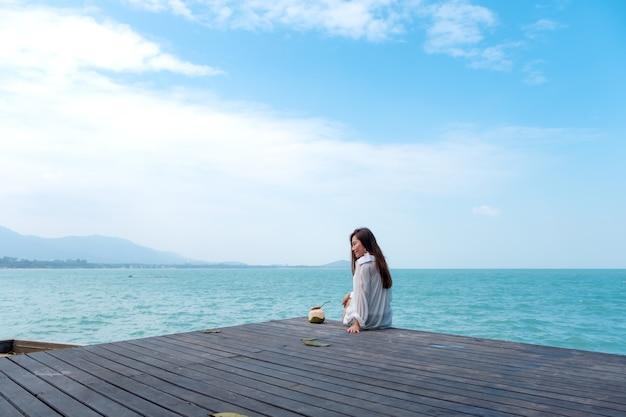 Mulher asiática sente-se à beira-mar