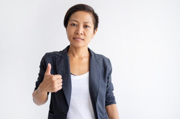 Mulher asiática séria aparecendo polegar
