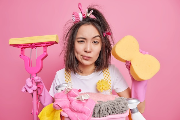 Mulher asiática séria com cabelo escuro parece fadiga segura a esponja e o esfregão vai lavar tudo no quarto se preocupa com poses de limpeza em roupas casuais perto do cesto de roupa suja. conceito de limpeza regular