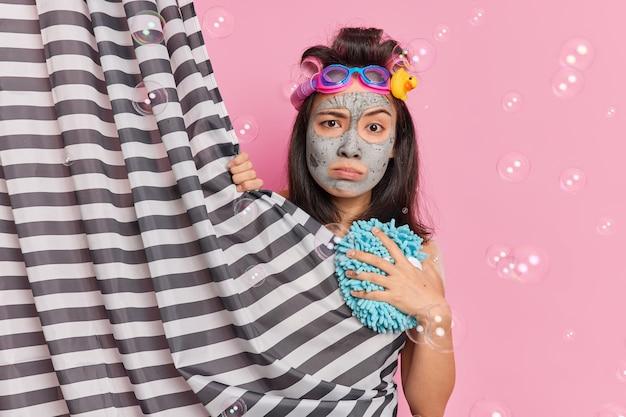 Mulher asiática séria descontente olha diretamente para a câmera se esconde atrás da cortina do chuveiro passa por procedimentos de beleza na ducha aplica poses de máscara facial de argila contra um fundo rosa com bolhas ao redor