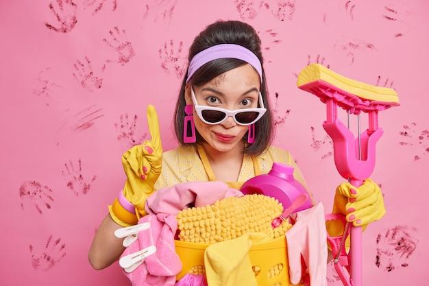 Mulher asiática séria parece que inspetor de limpeza levanta o dedo indicador tem expressão autoconfiante segura esfregão usa bandana luvas de borracha óculos de sol faz o trabalho doméstico remove toda a sujeira do quarto