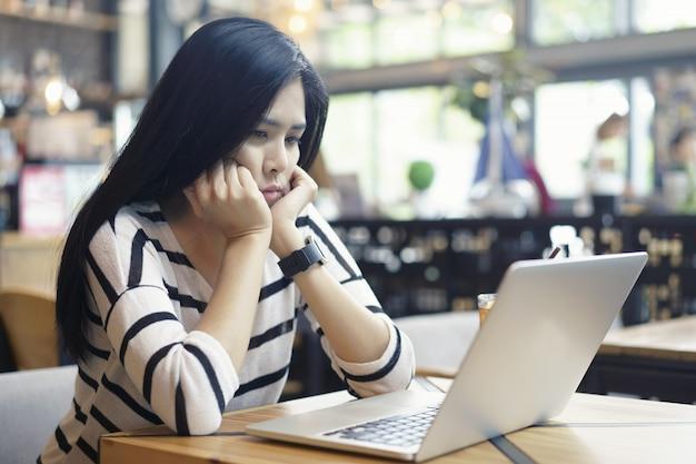 Mulher asiática séria pensando em problema para trabalhar uma tarefa difícil em um desktop