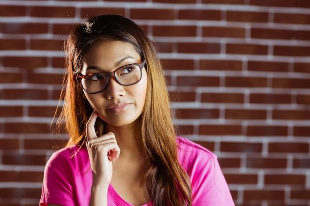 Mulher asiática séria pensando na parede de tijolo
