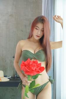 Mulher asiática sexy de biquíni verde segurando uma rosa vermelha no quarto