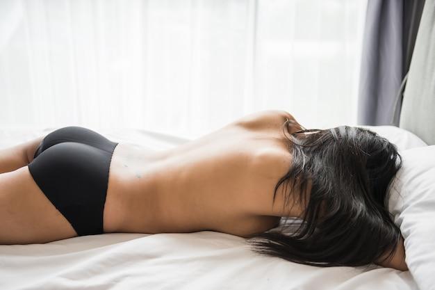 Mulher asiática sexy nua na cama