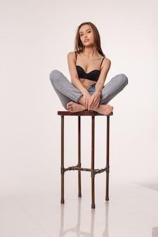 Mulher asiática sexy posando em lingerie preta jeans azul em um banquinho no estúdio