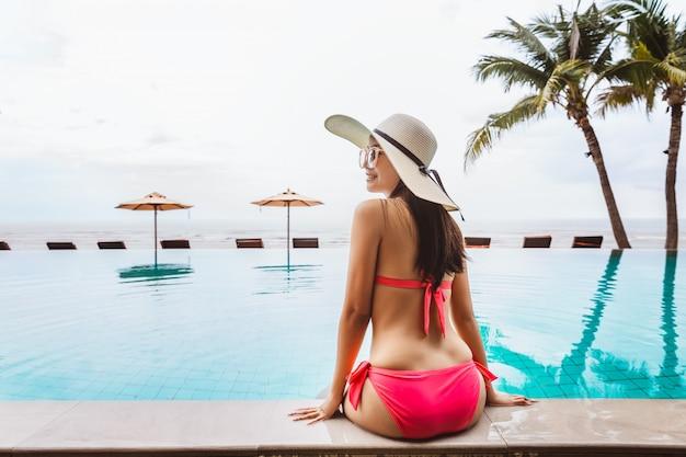 Mulher asiática sexy relaxar na piscina na praia, vista traseira