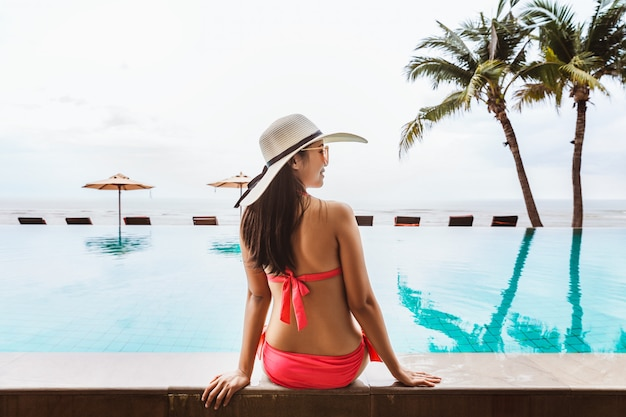 Mulher asiática sexy relaxar na piscina na praia
