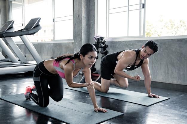 Mulher asiática sexy treino parte inferior da coxa em um tapete de ioga com o homem treinador no ginásio. conceito de exercício no ginásio. mulher e homem treino no tapete de ioga.