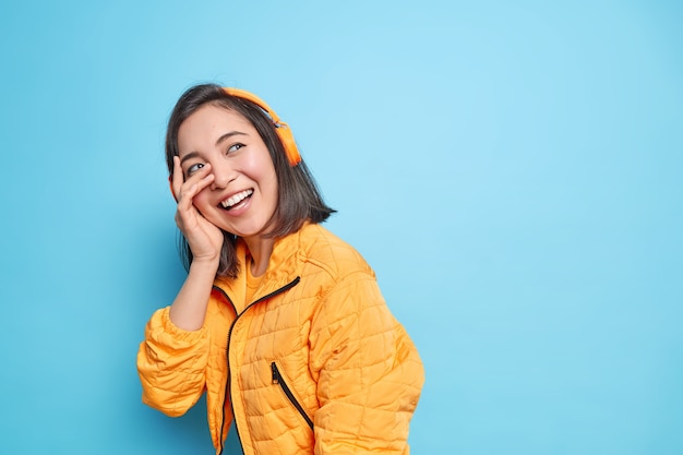 Mulher asiática sincera e despreocupada que faz o rosto sorrir com a palma da mão se diverte alegremente enquanto caminha na rua ouve música através de fones de ouvido sem fio tem modelos de humor feliz contra a parede azul com espaço em branco