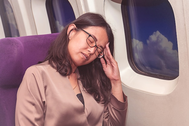 Mulher asiática sofre de dor de cabeça dentro do avião