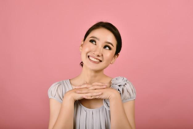 Mulher asiática sonhando acordada com um grande sorriso e feliz.