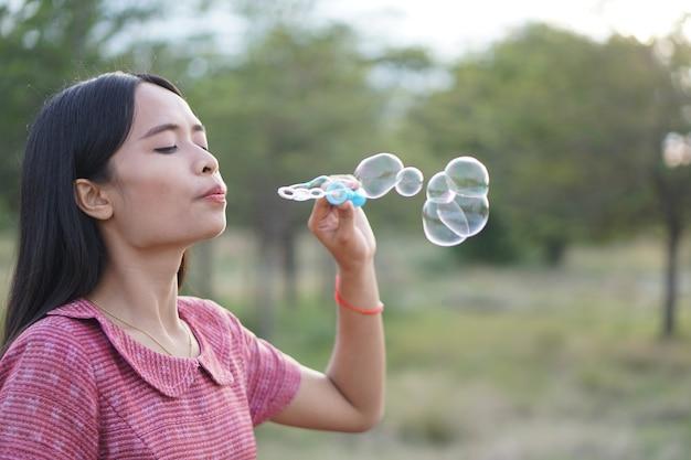 Mulher asiática soprando bolhas de sabão em cada fundo de grama verde
