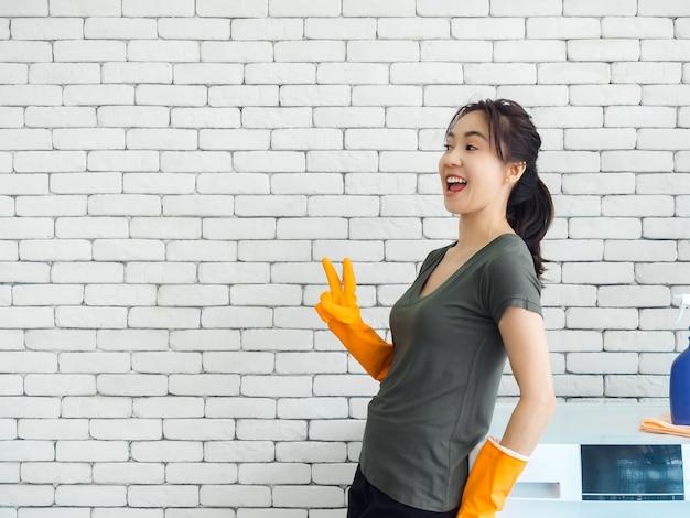 Mulher asiática sorridente, alegre e feliz, dona de casa usando luvas de borracha laranja mostrando dois dedos, sinal de vitória perto da máquina de lavar na parede de tijolos brancos