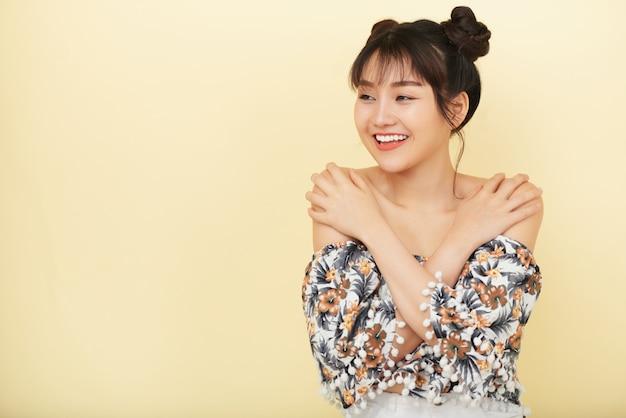 Mulher asiática sorridente com as mãos nos ombros, posando e olhando de lado