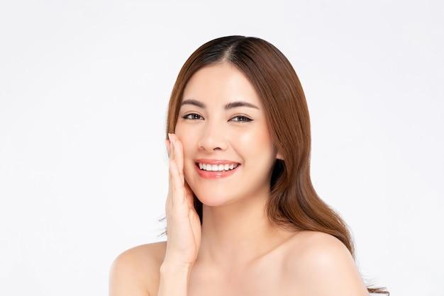Mulher asiática sorridente com mão de pele clara, tocando seu rosto