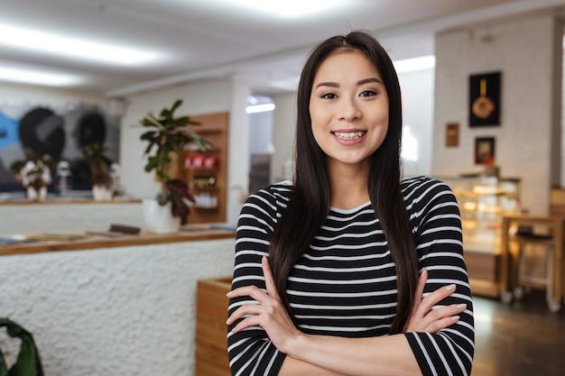 Mulher asiática sorridente com os braços cruzados na cafeteria