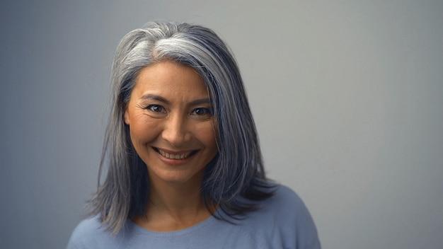 Mulher asiática sorridente com rugas perto dos olhos