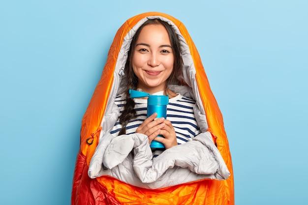 Mulher asiática sorridente com trança, embrulhada em saco de dormir, bebe chá quente da garrafa térmica, tenta se aquecer depois de caminhar no frio, passa a noite na natureza, desfruta de um descanso tranquilo e maravilhoso