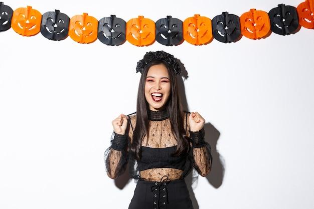 Mulher asiática sorridente despreocupada na fantasia de bruxa, aproveitando a festa de halloween, dançando e regozijando-se, em pé sobre um fundo branco com decoração de serpentinas de abóbora.