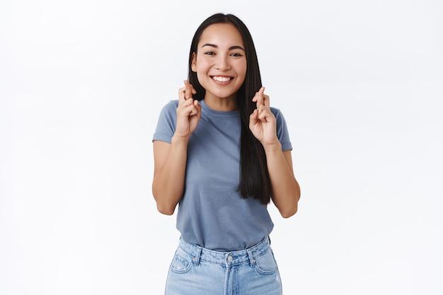 Mulher asiática sorridente e animada fiel fazendo um desejo, cruzar os dedos boa sorte, olhar determinado, câmera, acreditar que os sonhos se tornam realidade, suplicando, orando para alcançar a meta, aguardando resultados, parede branca
