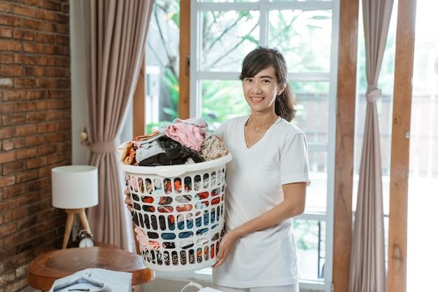 Mulher asiática sorridente e feliz carregando uma cesta de pano