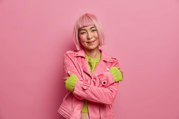Mulher asiática sorridente e terna com penteado tingido se ama, abraça o corpo, vestida com jaqueta casual