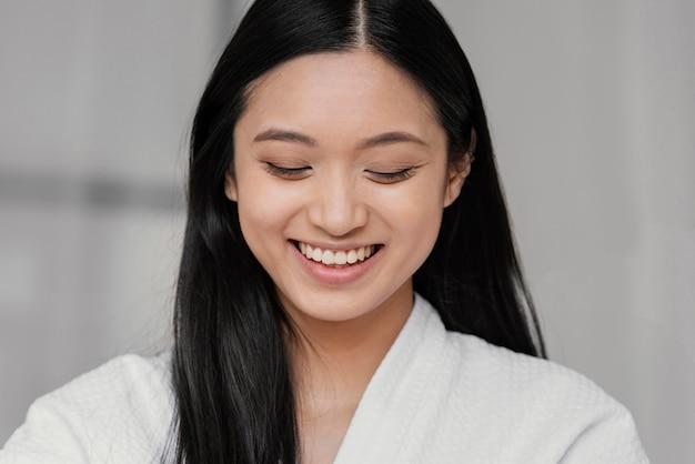 Mulher asiática sorridente em casa