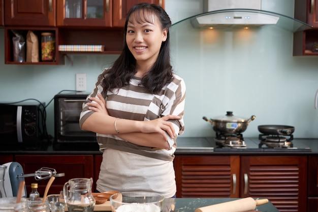 Mulher asiática sorridente em pé na cozinha e utensílios de cozimento, deitada na mesa
