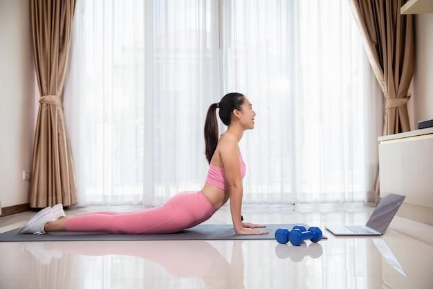 Mulher asiática sorridente em pose de cobra praticando ioga e assistindo a vídeos no laptop, treinando na sala de estar