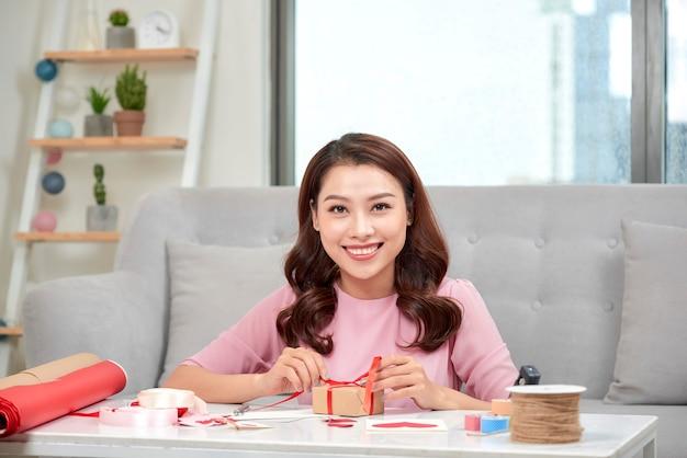 Mulher asiática sorridente embrulhando presentes para o feriado no fundo da sala de estar